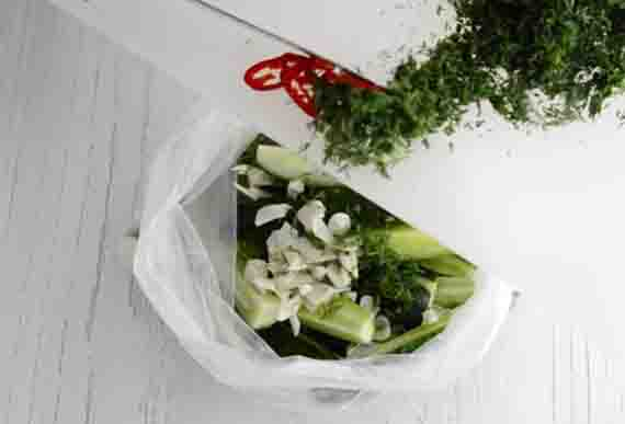 vykladyvanie zeleni v paket s ogurcami